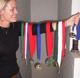 Pamela Strom showing her many medals on her arm